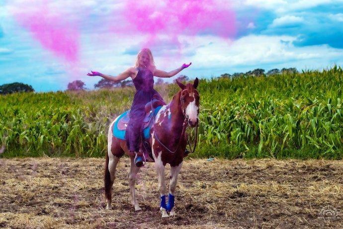 Sarah mit rotem Holi Pulver auf ihrem Pferd
